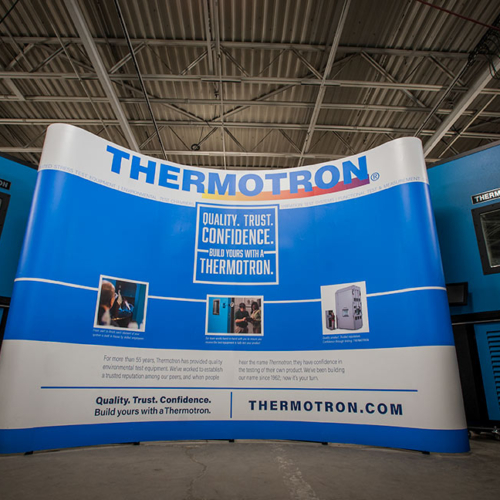 "The curved trade show display creates an inviting atmosphere, highlights the three reasons customers choose Thermotron, and incorporates the current tagline ""Quality. Trust. Confidence. Build yours with a Thermotron."""