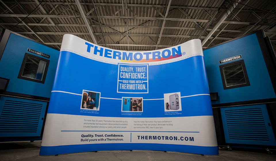 """The curved trade show display creates an inviting atmosphere, highlights the three reasons customers choose Thermotron, and incorporates the current tagline """"Quality. Trust. Confidence. Build yours with a Thermotron."""""""